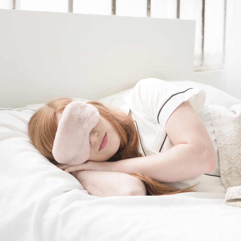 Woman sleeping with mask over eyes for darkness